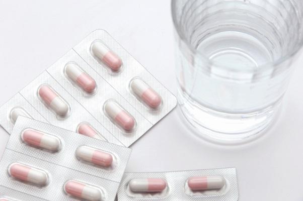 白とピンクの錠剤のと水の入ったコップ