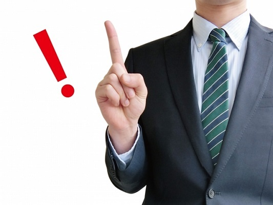 人差し指を立てるスーツ姿の男性